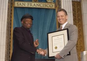 """Vid denna begivenhet överlämnade San Franciscos borgmästare Willie Brown (till vänster), en proklamation till kyrkan """"för dess ansträngningar att göra området runt San Francisco-bukten till en bättre plats för personer av alla hudfärger, trosuppfattningar och från alla samhällsskikt."""""""